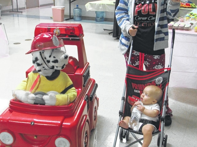 Danae King   The Lima News A Lima Fire Department fire inspector voices an animated fire dog as it speaks to a baby at the Community Baby Shower on Saturday.