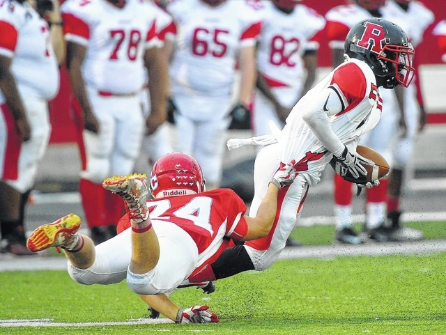 Richard Parrish   The Lima news Sammy Santaguida of Lima Central Catholic makes a diving tackle on Mike Moore of Toledo Rogers during Saturday's game at Spartan Stadium.