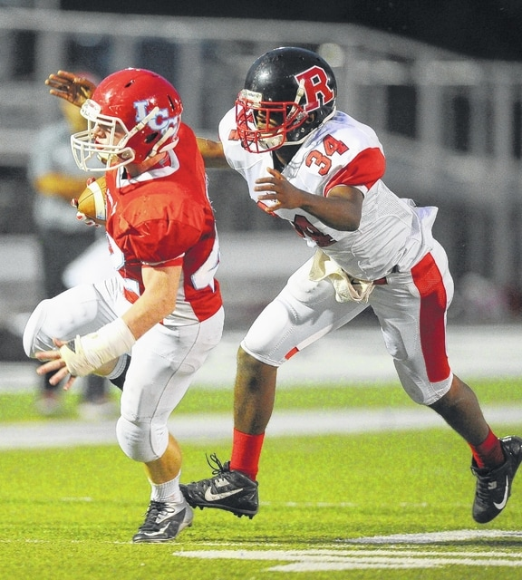 Richard Parrish   The Lima News Tate Lamb of Lima Central Catholic rushes ahead of Bryson Powell of Toledo Rogers during Saturday's game at Spartan Stadium.