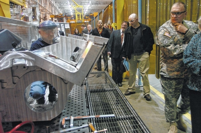 A group takes a tour through the Joint Systems Manufacturing Center in 2012. The facility, once threatened with closure, has seen good news in recent months.