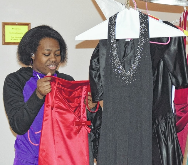 Vi'shaan Cummings, a senior at Lima Senior High School, looks at prom dresses during an event managed by the Kiwanis Club, which gives girls prom dresses at no cost.