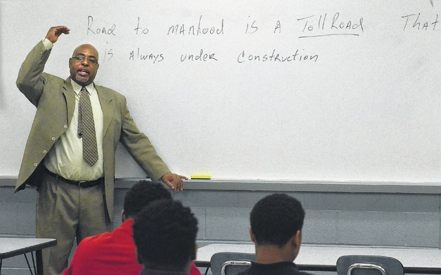 "Bryan Miller, director of Lima schools' ""Closing the Achievement Gap"" program, explains a quote on the whiteboard, ""Road to manhood is a toll road that is always under constructions."" CTAG, an initiative originally designed in 2007 for black males at risk of not graduating high school, expanded to help any at-risk student. When the program started, only 47 to 48 percent of black males were graduating from Lima schools. Since implementing CTAG eight years ago, that number has averaged 78 percent."