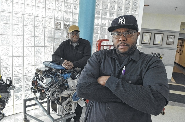 """Lydell Jackson, foreground, stands in the Ford Engine Plant education center with his father, Eugene Jackson, who retired from Ford several years ago. Lydell noted that the job market was much different for his father in the 1950s and '60s. """"My dad, he could leave one high paying job today and be in another high paying job the same day, because that was the boom of the economy. Now, the job market isn't the same. It's just not the same."""""""