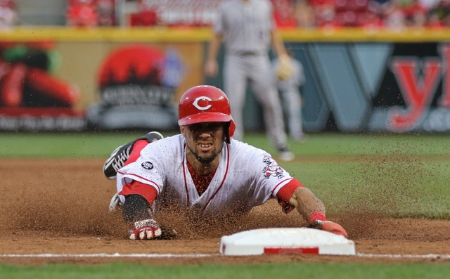 Cincinnati Reds' Billy Hamilton slides into third base with a steal against the Colorado Rockies during the second inning of a baseball game, Tuesday, April 19, 2016, in Cincinnati. (AP Photo/Gary Landers)