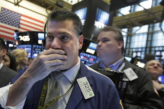 Trader William McInerney, left, works on the floor of the New York Stock Exchange, Wednesday, April 20, 2016. U.S. stock indexes are narrowly mixed in early trading on Wall Street as investors absorb the latest round of company earnings reports. (AP Photo/Richard Drew)