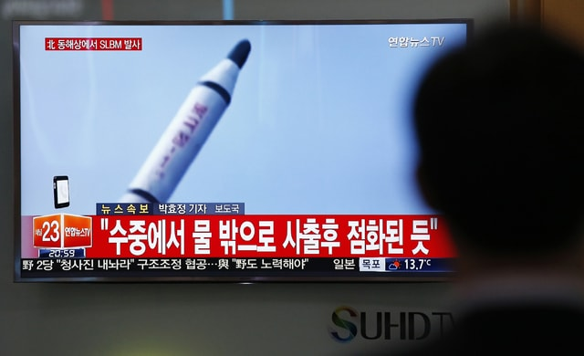"""A man watches a TV news program showing a file footage of a missile launch conducted by North Korea, at the Seoul Train Station in Seoul, South Korea on Saturday. North Korea on Saturday fired what appeared to be a ballistic missile from a submarine off its northeast coast, South Korean defense officials said, Pyongyang's latest effort to expand its military might in the face of pressure by its neighbors and Washington. The Korean letters at top left read: """"North Korea fires a submarine-launched ballistic missile or SLBM."""""""