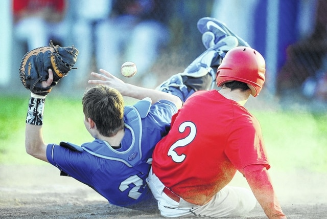 Bluffton's Braeden Edwards slides safely into home plate before Allen East's Matt Fish get him out during Tuesday's game in Bluffton.