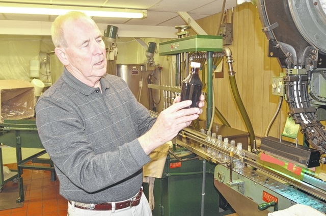 H&K Products co-owner Don Nordhaus inspects a bottle of Pappy's Sassafrass Tea after it is capped on the production line in a warehouse in Columbus Grove.