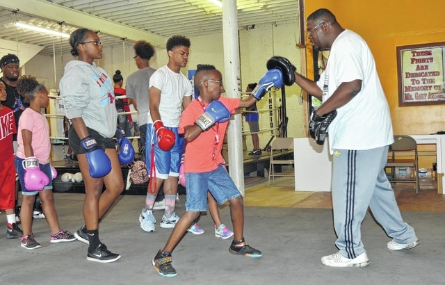 Ashton Smith, 10, boxes with New Look Fitness owner Aaron McLaurine as part of Lima UMADAOP's summer youth program. Through the program, young people are able to participate in physical activites like boxing as an alternative to drug and alcohol use.