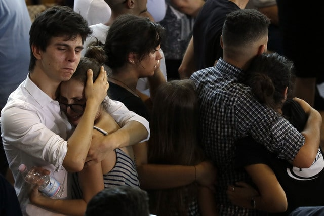 Relatives and friends mourn during the state funeral service of some of the earthquake victims in Ascoli Piceno, Italy, Saturday, Aug. 27, 2016. Funerals for some victims took place on Friday, while those for many others are expected in the coming days. (AP Photo/Gregorio Borgia)