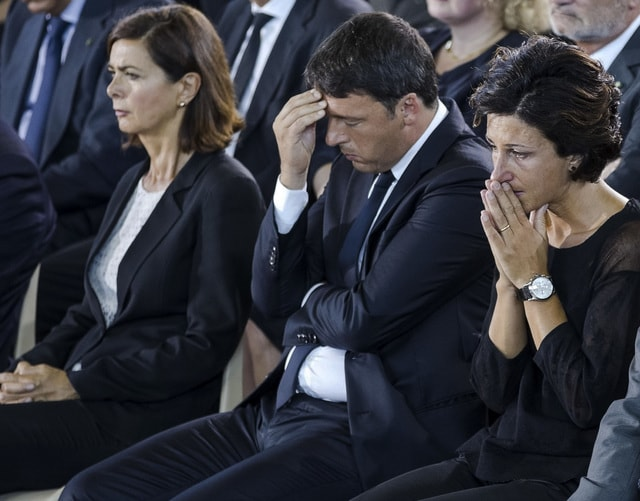 From left, Italian Lower House Speaker Laura Boldrini, Premier Matteo Renzi and his wife Agnese Landini attend the mass funeral in Ascoli Piceno, central Italy, Saturday, Aug. 27, 2016, for some of the victims of the earthquake that devastated the region on Wednesday. Residents of an Italian region devastated by an earthquake were rattled by a series of aftershocks overnight, the strongest measuring 4.2, as Italy began a day of national mourning on Saturday. (Massimo Percossi/ANSA via AP)