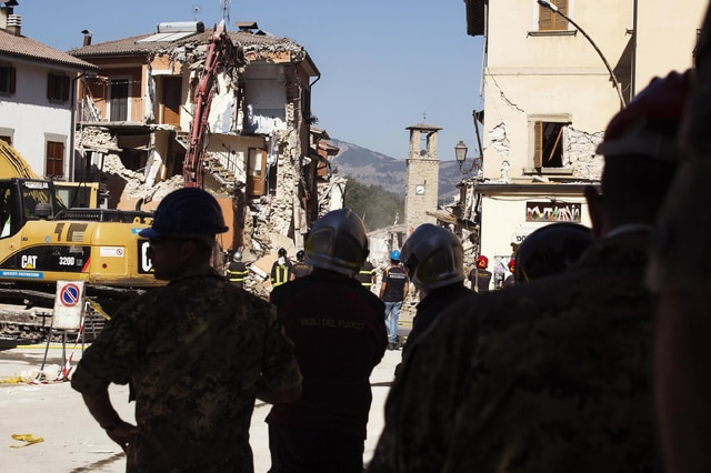 Firefighters work in Amatrice, central Italy, Sunday, Aug. 28, 2016. Bulldozers with huge claws pulled down dangerously overhanging ledges Sunday in Italy's quake-devastated town of Amatrice as investigators worked to figure out if negligence or fraud in building codes had added to the quake's high death toll. (Roberto Salomone/ANSA via AP)