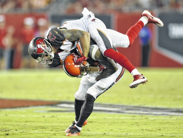 Tampa Bay Buccaneers strong safety Chris Conte (23) jumps on Cleveland Browns wide receiver Terrelle Pryor (11) after a reception during the second quarter of an NFL preseason football game Fridayin Tampa, Fla.