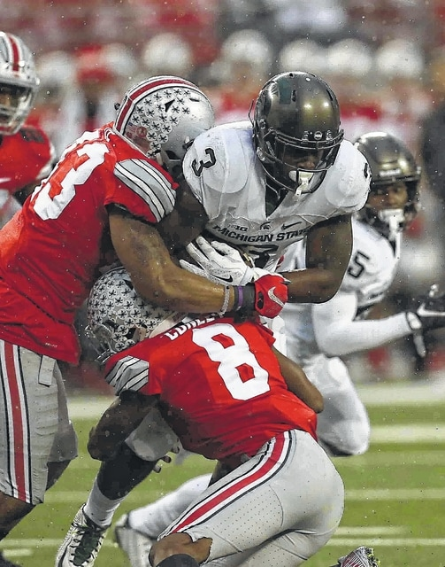 Gareon Conley (8) and Darron Lee (43) wrap up Michigan State running back L.J. Scott (3) during a game last season in Ohio Stadium. DON SPECK/The Lima News