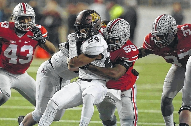 OSU #43 Darron Lee (left) OSU #59 Tyquan Lewis (middle) and OSU #37 Eli Apple combine to stop  Minnesota #24 Rodney Smith for a loss in the first quarter At Ohio Stadium on the campus of The Ohio State University November 7,2015