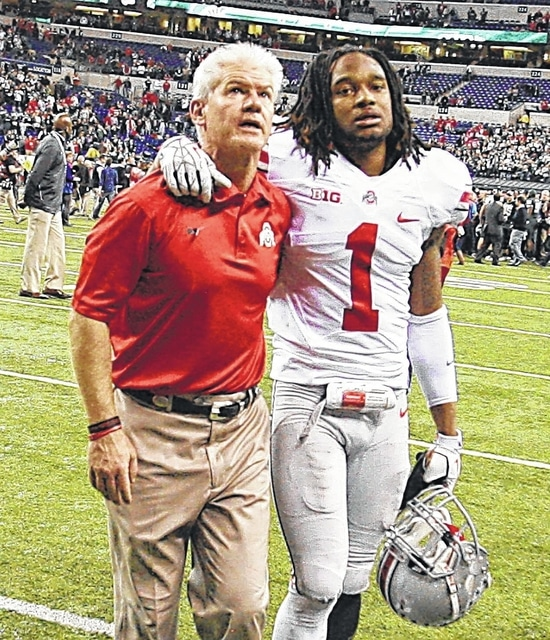 Assistant coach Kerry Coombs and Bradley Roby (1) walk off the field after Ohio State's loss to Michigan State in the 2013 Big Ten championship game. DON SPECK/The Lima News