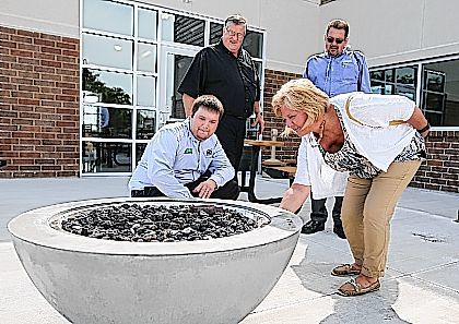 University of Northwestern Ohio staff check out the new fire pit after the ribbon-cutting ceremony and grand opening held for the new student club, Racers Station, on Tuesday morning.