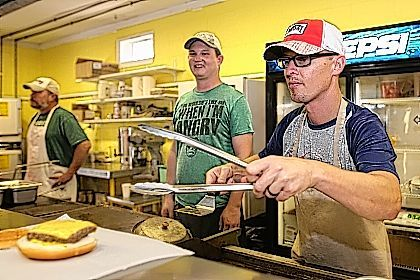Volunteer Adam Walls, of Lima, right, prepares a burger at the Bath Band Boosters Food Den during the Allen County Fair on Tuesday evening.