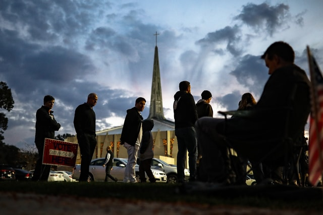 Adam Fohlen and his son Ari, center left, wait in line outside a polling place at the Nativity School as a poll watcher who refused to be identified sits nearby, Tuesday, Nov. 8, 2016, in Cincinnati. (AP Photo/John Minchillo)