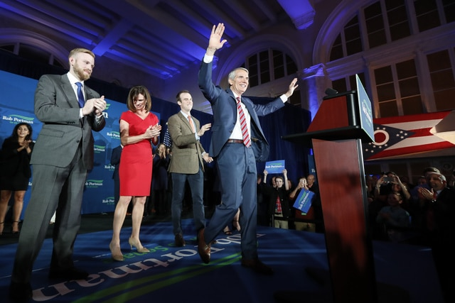 Sen. Rob Portman, R-Ohio, center, celebrates with his son Jed, left, wife Jane, second from left, and son Will, center left, during an election night rally at The Vault, Tuesday, Nov. 8, 2016, in Columbus, Ohio. (AP Photo/John Minchillo)