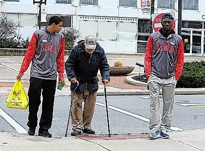 Lima Senior's Marquis Coleman, left, and Jarius Ward, right, assist Carl Dienstberger across the street during Thursday's Lewis Family McDonalds Thanksgiving Day Dinner held at the Lima Veterans Memorial Civic and Convention Center. Richard Parrish | The Lima News