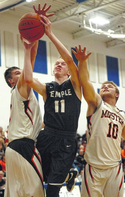 Temple Christian's Seth Hohlbein goes up for a shot against Minster's Bryce Schmiesing (10) and Jarod Schulze during a Division IV sectional final at Allen East.