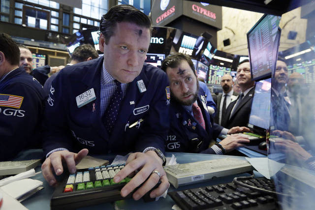 Specialists Gregg Maloney, left, and Michael Pistillo work at their post near the close of trading on the floor of the New York Stock Exchange, Wednesday, March 1, 2017. Banks and other financial companies led U.S. stocks sharply higher, pushing the Dow Jones industrial average to close above 21,000 points for the first time. (AP Photo/Richard Drew)