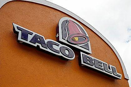 """This May 23, 2014, file photo shows a sign at a Taco Bell in Mount Lebanon, Pa. The chain's """"Love and Tacos"""" contest offers couples the chance to win an all-expense paid trip to Las Vegas to get married in a chapel at the chain's flagship restaurant. The winner will be announced March 16."""
