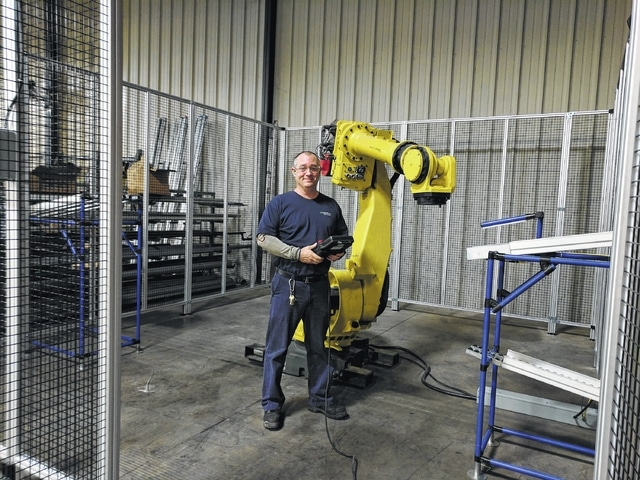 """Chad Adkins, a project engineer at Whirlpool in Ottawa, works with a robotic device. The company participates in """"Work, Earn and Learn"""" program to attract and train younger employees."""