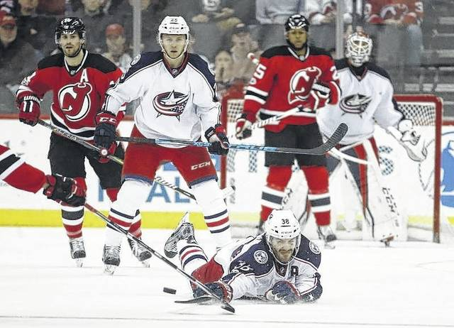 Columbus Blue Jackets center Boone Jenner falls to the ice while trying to deflect a shot by the New Jersey Devils during the first period of an NHL hockey game, Sunday in Newark, N.J.