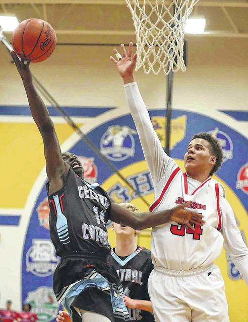 Lima Central Catholic's Jaron Banks puts up a shot against Delphos Jefferson's Davion Tyson during a Wednesday night Division III sectional game at St.Marys.