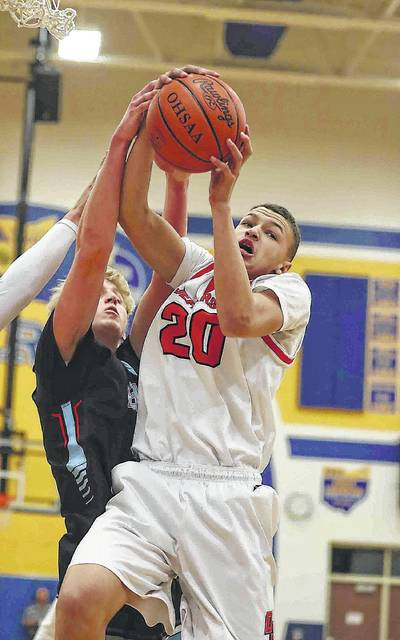 Delphos Jefferson's Tyler Bratton pulls down a rebound against Lima Central Catholic's Mark Janowski during a Wednesday night Division III sectional game at St. Marys.