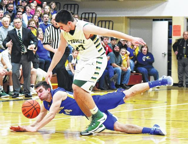 Continental's Wade Stauffer dives for a loose ball against Ottoville's Nick Moorman during a Friday night Division IV sectional final at Ottawa-Glandorf.