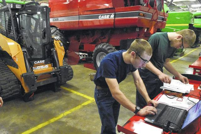 Using a laptop and owner's manual, Joshua Hoenie, 16, left, and Ken Bertke, 17, students from Coldwater High School, trouble-shoot for an electrical problem on a Case TR310 Skid Steer during the University of Northwestern Ohio State of Ohio Agricultural Power Diagnostics CDE contest on Friday.