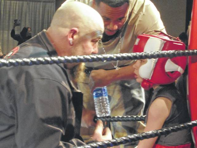 Eight-year-old Aiden Vogt, right, gets instructions from his coach, Matt Vogt, who is also his father. Aiden secured a three-round victory at Fight Night at the Veterans Memorial Civic and Center on Saturday.