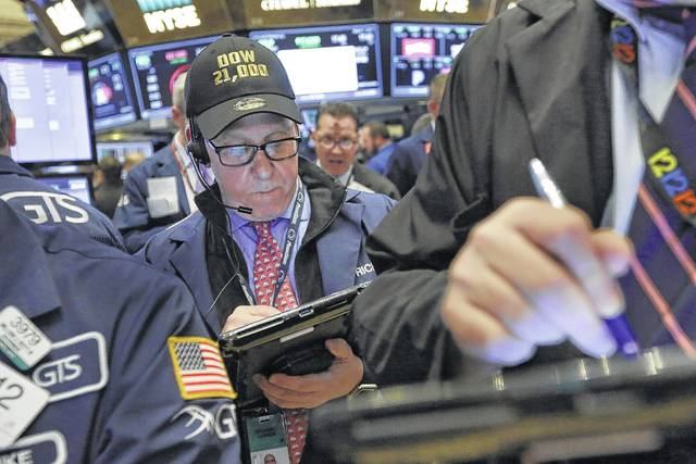 """FILE - In this Wednesday, March 1, 2017, file photo, trader Richard Cohen wears a """"Dow 21,000"""" cap as he works on the floor of the New York Stock Exchange. Excitement that President Donald Trump will drive business-friendly policies is only one of the reasons behind the stock market's recent surge. The economy is getting stronger, and so are corporate profits."""