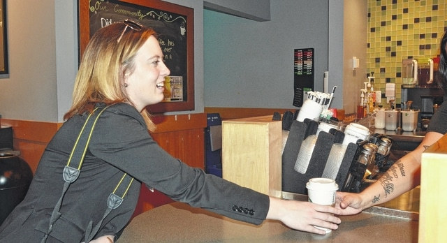 Courtney O'Banion, communications coordinator at St. Rita's Medical Center, grabs a Starbucks coffee at the hospital. The 27-year-old said having a Starbucks inside the facility is a nice perk, and her fellow Millennial workers appreciate having a cafe within the building.