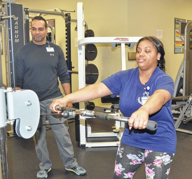 Dynerica Dennard, a 29-year-old patient transport employee at St. Rita's Medical Center, works out at the hospital's fitness center as fitness coordinator Abe Frieson looks on. Dennard said she enjoys being able to work out without having to leave the building.