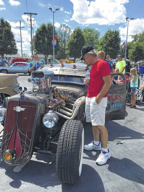 Brent Rankin, of Lima, looks over the engine of Dave Webb's Rat Rod at the ninth annual Westgate Charity Car Show.