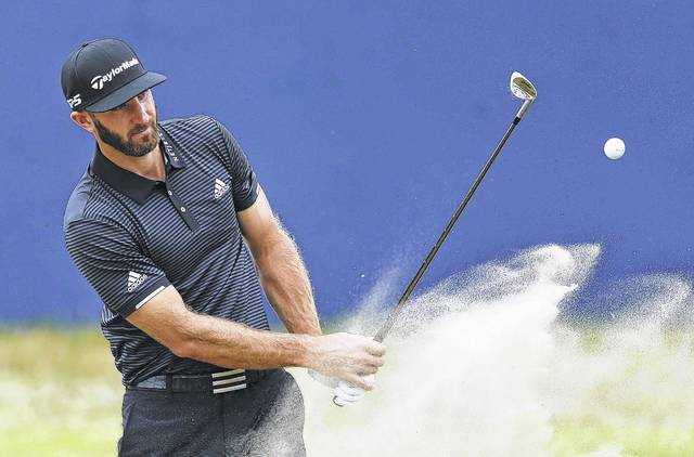 Dustin Johnson, one of the favorites entering today's first round of the British Open, plays out of the bunker on the 18th hole during a Wednesday practice round at Royal Birkdale, Southport, England.