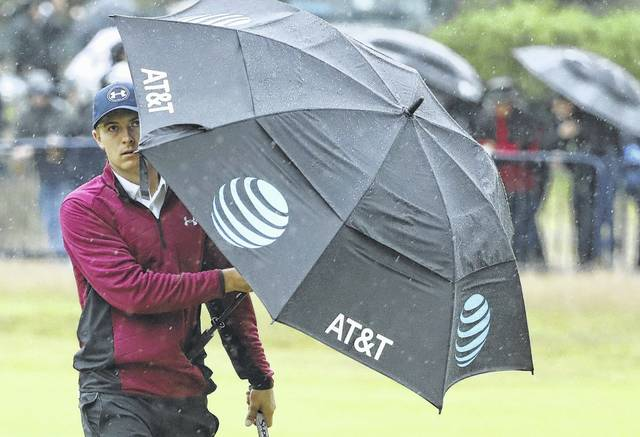 Jordan Spieth uses an umbrella to block the wind and rain while walking along the 18th fairway during Friday's second round of the British Open Golf Championship at Royal Birkdale in Southport, England.