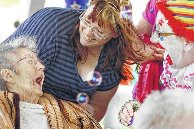 "Martha Kohler (left) enjoys blowing bubbles Saturday with Margie Wireman (center) a nurse's aide for Cridersville Healthcare Center, and Margaret ""Chris"" Mills, a clown with Happy's Family Clown Group, after watching the Cridersville Fireman's Jamboree parade last year."
