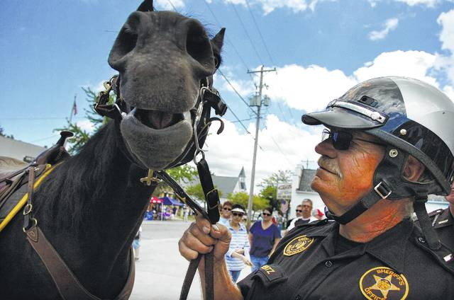 Jim Clementz, a lieutenant with the Allen County Sheriff's mounted posse unit, stands with his horse Walker before the blessing of the badges during last year's Cridersville Fireman's Jamboree in Cridersville.
