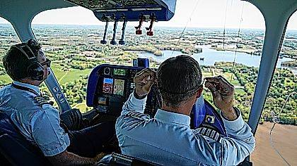 In this Monday, May 15, 2017, photo, Michael Doughtery, right, chief Goodyear pilot, lifts his earpiece off during an airship training flight for William Bayliss, left, over Akron, Ohio. The Goodyear Tire company is training pilots of its iconic blimps to fly new airships in northeast Ohio. Goodyear retired the last of its old blimp fleet in March. (AP Photo/Dake Kang)