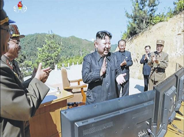 This image made from video of a news bulletin aired by North Korea's KRT on Tuesday shows what was said to be North Korea leader Kim Jung Un, center, applauding after the launch of a Hwasong-14 intercontinental ballistic missile in North Korea's northwest.