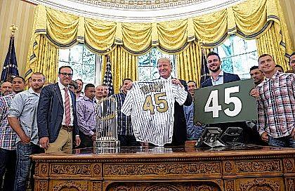 """FILE - In this June 28, 2017, file photo, President Donald Trump meets with Albert Almora (far right) and other members of the 2016 World Series Champions Chicago Cubs in the Oval Office of the White House in Washington. Cubs third baseman Kris Bryant holds the other """"45"""" sign. Almora denied making an offensive gesture to the president during the meeting. (AP Photo/Susan Walsh, File)"""