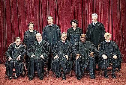 FILE - In this June 1, 2017, file photo, the justices of the U.S. Supreme Court gather for an official group portrait to include new Associate Justice Neil Gorsuch, top row, far right at the Supreme Court Building in Washington. Seated, front row, from left are, Associate Justice Ruth Bader Ginsburg, Associate Justice Anthony M. Kennedy, Chief Justice of the United States John Roberts, Associate Justice Clarence Thomas, and Associate Justice Stephen Breyer. Back row, standing, from left are, Associate Justice Elena Kagan, Associate Justice Samuel Alito Jr., Associate Justice Sonia Sotomayor, and Associate Justice Neil Gorsuch. The AP reported on July 7, 2017, that a story claiming White House Press Secretary Sean Spicer said President Donald Trump had the power to disband the court was a hoax. (AP Photo/J. Scott Applewhite, File)