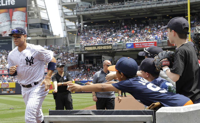 New York Yankees right fielder Aaron Judge, left, jogs by as a fan wearing a t-shirt with his name and number tries to get an autograph prior to an interleague baseball game against the Milwaukee Brewers Saturday at Yankee Stadium in New York. Bryce Harper, Mike Trout and Aaron Judge have become the face of baseball as a gleaming, modernist ballpark and a city known for its Latino culture host the All-Star Game for the first time.