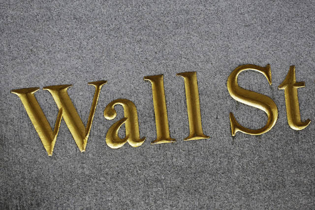 FILE - This Monday, July 6, 2015, file photo shows a sign for Wall Street carved into the side of a building in New York. Stocks are off to a mixed start on Wall Street, Tuesday, July 11, 2017, as losses for big department stores and materials companies outweigh gains in health care. (AP Photo/Mark Lennihan, File)