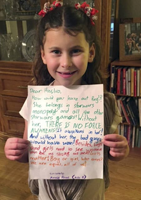 "In this January 2016 photo provided by Carrie Goldman, her daughter, Annie Rose, holds a letter in Evanston, Ill., that she wrote to Hasbro asking why the female character Rey was omitted from a Monopoly set based on ""Star Wars: The Force Awakens,"" when she is a main character and crucial to the story. Hasbro responded that they would add Rey to a Star Wars version of Monopoly by the end of the year. Eighteen months later, Annie Rose and others are still waiting."